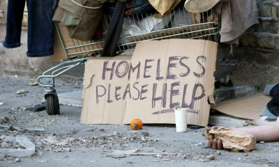 Picture of homeless person with sign that says please help.